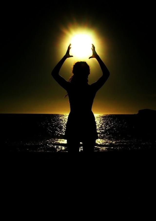 Sun in hands in dark ocean