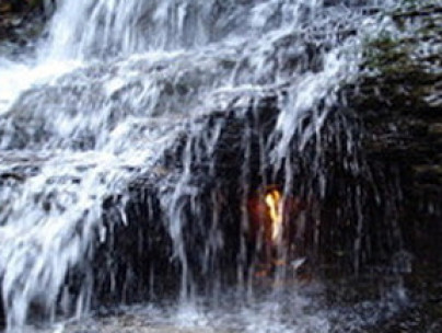 Fire burning naturally in midst of waterfall